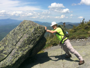 The author, trying to tip a boulder off the summit of Mount Colden, wearing The Mountaineer.