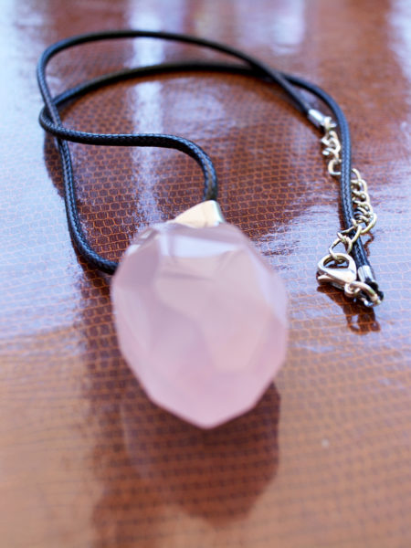 A beautifully handmade pink quartz pendant made of a large pink quartz stone, quality waxed thread and Sterling Silver plated clasp and chain.