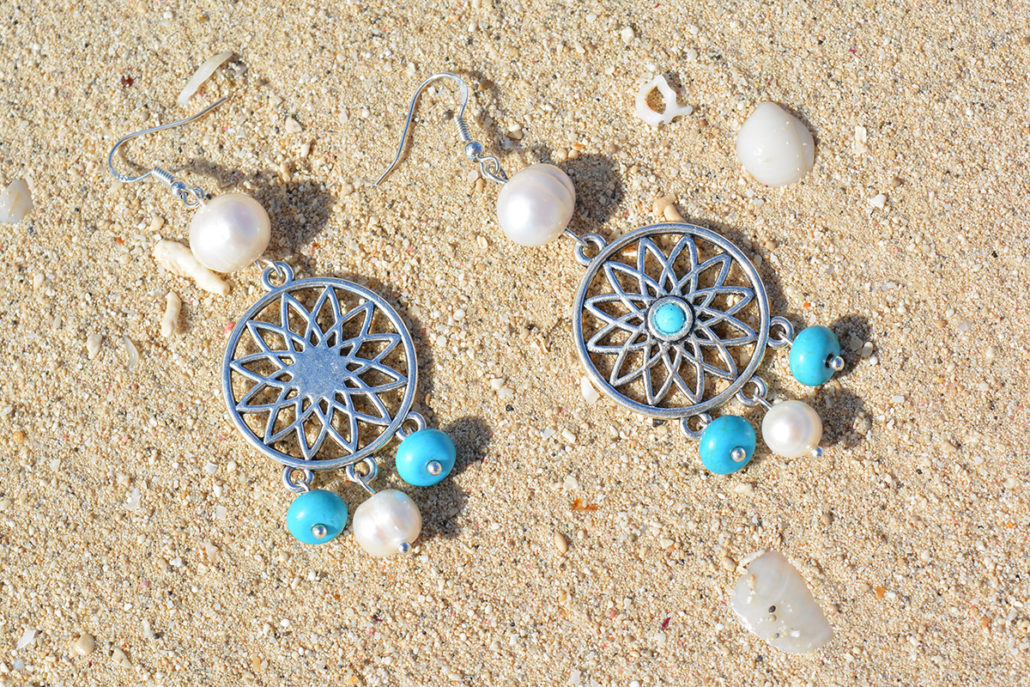 Picture of a set of Unikgemz Colonial Earrings lying in the sand on a Caribbean beach in Cuba.
